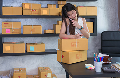 young woman addressing a box for mailing