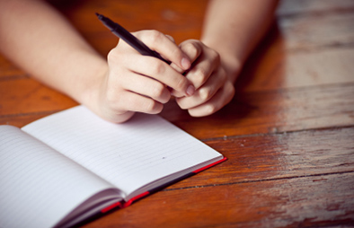 Person holding pencil in hands on top of a blank journal