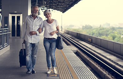 Older couple walking at a train station.