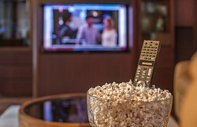A bowl of popcorn with a remote in front of a TV