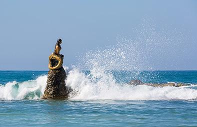 Mermaid statue with waves crashing against it
